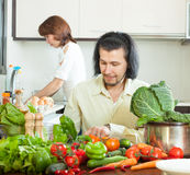 A woman and handsome man with vegetables in the kitchen Royalty Free Stock Photo