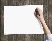 Woman& x27; handstil för hållande penna för s-hand på tom vitbok arkivfoton