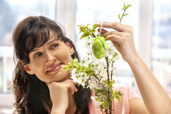 Woman hang easter egg on cherry branch. Stock Photo