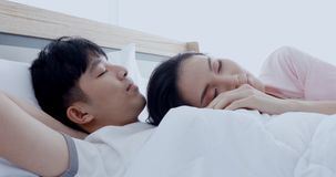 Woman hang the head at his chest, he rub her head. Asian couple are lying in bed, woman pulling blanket to cover, and she putting the head at the boyfriend`s stock footage