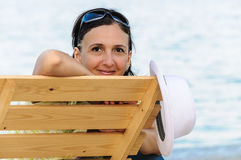 Woman hanged white hat in lounge chair Royalty Free Stock Image