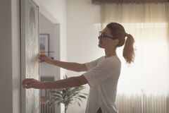 Free Woman Hanging A Painting At Home Royalty Free Stock Images - 191518829