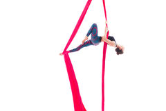 Woman hanging in aerial silks, isolated on white Stock Photos