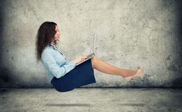 Woman hanging in the air with laptop Stock Image
