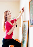 Woman hanging the art pictures on wall Royalty Free Stock Photography