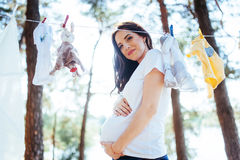 Woman hanging baby clothes in linen rope outdoors Royalty Free Stock Photo