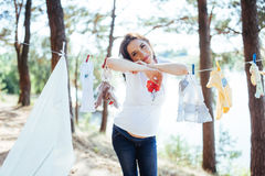 Woman hanging baby clothes in linen rope outdoors Royalty Free Stock Photography