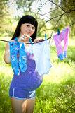 Woman hanging baby laundry Stock Image