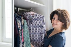 Woman hanging a blouse in closet on hanger. Woman hanging a blouse in a closet on a hanger royalty free stock image