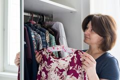 Woman hanging a blouse in closet on hanger. Woman hanging a blouse in a closet on a hanger royalty free stock images