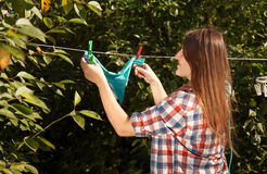 Woman hanging blue bikini on clothesline at garden Royalty Free Stock Image