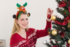Woman hanging christmas decorations on tree Royalty Free Stock Image
