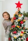Woman hanging Christmas top on Christmas tree Royalty Free Stock Photo