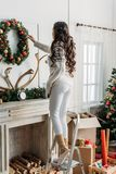 Woman hanging christmas wreath over fireplace. While standing on stepladder Royalty Free Stock Photo