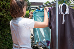 Woman hanging clothes on dryer at home Royalty Free Stock Image