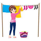 Woman Hanging Clothes. Happy young woman hanging wet clothes out to dry Royalty Free Stock Photo