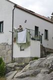 Woman hanging  clothes on the terrace Stock Photography