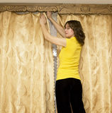 Woman hanging curtains Royalty Free Stock Photos
