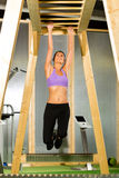 Woman hanging at high or horizontal bar Stock Photo