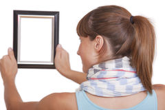 Woman hanging photo frame Royalty Free Stock Photos