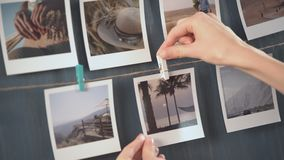 Woman hanging photo of her travel on the wall, vacation photos.  stock footage