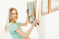Woman hanging picture with flowers on wall at home. Positive blonde woman hanging picture with flowers on wall at home stock image