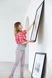 Woman hanging picture frame on wall in new house Stock Image