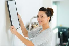 Woman hanging picture on wall stock image