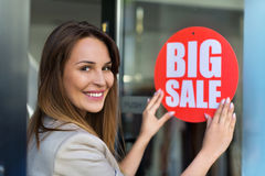 Woman hanging sale sign on door. Young woman hanging sale sign on door Royalty Free Stock Image