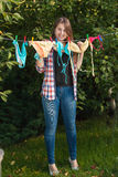 Woman hanging swimsuits on clothesline at garden Royalty Free Stock Photos