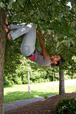 Woman Hanging from a Tree. A pretty young woman playfully hangs from a tree limb Royalty Free Stock Images