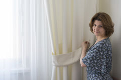 Woman hanging up his white curtains at window Stock Photos