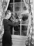 Woman hanging up a holiday wreath Stock Photos