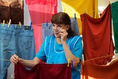 Woman hanging washed clothes and holding glasses Royalty Free Stock Image