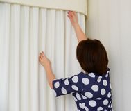 Woman hanging white curtains on window in apartment Royalty Free Stock Photography