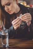 Woman with hangover with medicines in messy room Stock Images