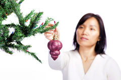 Woman hangs Christmas ornament. Royalty Free Stock Image