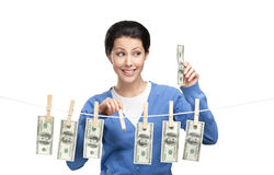 Woman hangs dollars on the line. With clothespins, isolated on white Royalty Free Stock Images