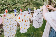 A woman hangs up baby clothes on a clothesline against the background of trees and grass bokeh royalty free stock photography