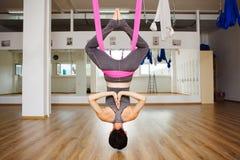 Woman hangs upside down doing aero anti gravity yoga exercises Stock Photography