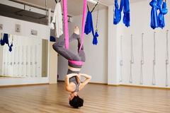 Woman hangs upside down doing aero anti gravity yoga exercises Royalty Free Stock Images