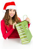 Woman happily opening her christmas gift bag Stock Photography
