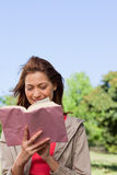 Woman happily reading a book with the wind blowing through her h Stock Photos