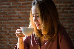 A beautiful woman is drinking coffee with satisfaction royalty free stock images