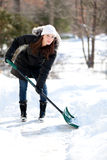 Woman happily shoveling snow. An attractive young woman smiling while shoveling snow Stock Images