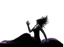 Woman happy awekening sitting in bed silhouette Stock Photo