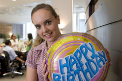 Woman with 'Happy Birthday' balloon, smiling, portrait Stock Image