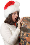 Woman happy with Christmas present. Young woman happily shocked when she opens a Christmas present; isolated on a white background Stock Image