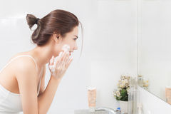 Woman happy cleanses the skin with foam in bathroom. Royalty Free Stock Photos