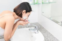 Woman happy cleanses the skin with foam on sink. stock images